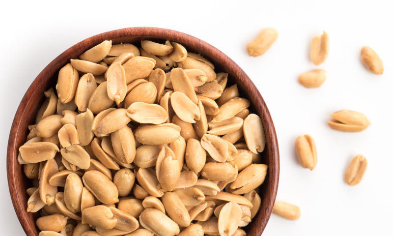Roasted salted peanuts in wooden bowl on white background,top vi